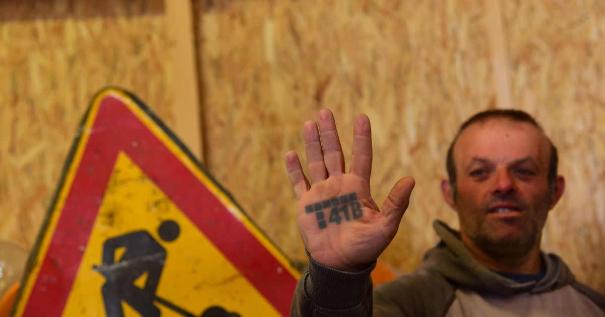 Lavoratore con scritto T41B sul palmo della mano